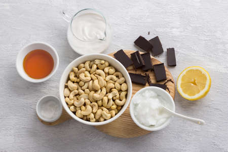 Ingredients for delicious vegan chocolate cashew cheesecake: cashews, chocolate, coconut oil, coconut cream, Jerusalem artichoke syrup, lemon and salt on light gray background, top view, flat lay Archivio Fotografico