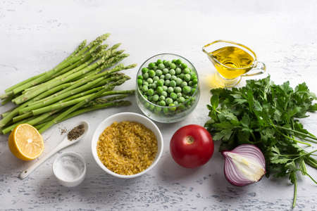 Ingredients for a middle eastern tabbouleh salad. Bulgur, fresh young green asparagus, green peas, tomato, red onion, herbs, lemon, olive oil and spices on a light blue background, top view. Healthy vegan food
