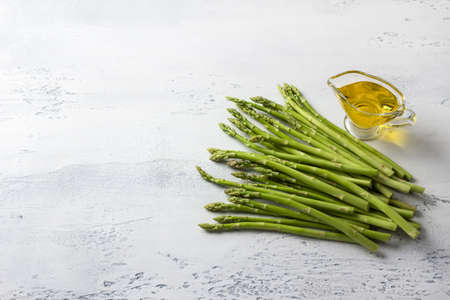 Fresh young asparagus with olive oil on light gray background, top view, copy space