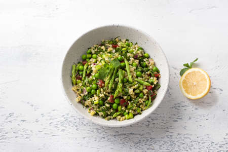 Traditional middle eastern or arabic tabbouleh salad of bulgur, tomatoes, asparagus, green peas and greens with half a lemon on a light gray background, top view. Healthy homemade vegan food
