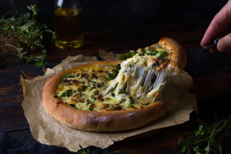 Delicious homemade pizza with asparagus, mushrooms, cheese and thyme on dark background. Slice of pizza with stretching cheese being on baking paper