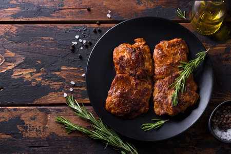 Fried vegan soy steak with rosemary, salt and pepper on black plate on wooden background, top view, free space Archivio Fotografico