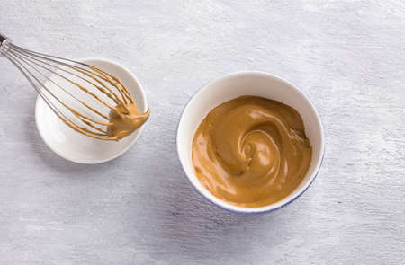 Ceramic bowl and whisk with fluffy creamy whipped coffee foam on a light gray textured background. For dalgona coffee, trendy food and drink concept