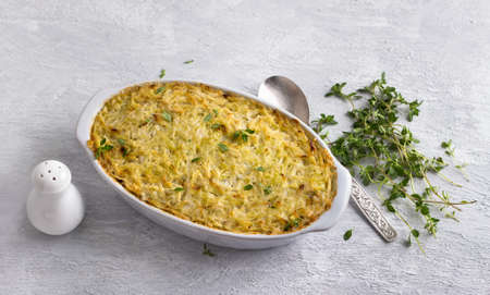 Cabbage casserole with lentils and cream, garnished with thyme in a ceramic baking dish on a light gray background, top view Archivio Fotografico