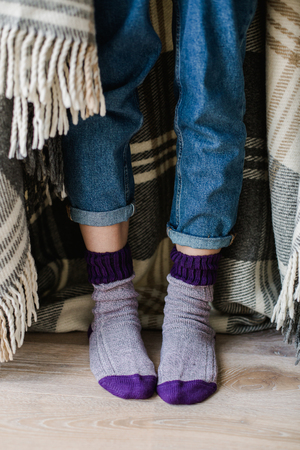 Feet in woollen socks. Woman is relaxing with a cup of hot drink and warming up her feet in woollen socks. Close up on feet. Winter and Christmas holidays concept.