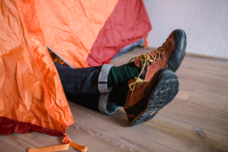 Feet in woollen socks. Man is relaxing near tent and warming up his feet in woollen socks.