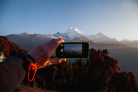 A man hands holding mobile take photo holding smartphone taking photo at mountain view. Фото со стока