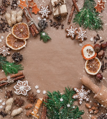 Frame with fir branches, cookies and Christmas decorations on dark brown paper background. Top view.