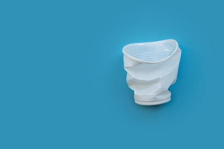 Bicchiere di plastica bianco sgualcito su sfondo blu come simbolo di inquinamento ambientale. Di' no alla plastica con un solo utilizzo.