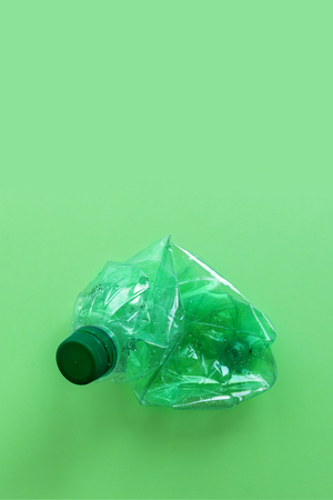 Used plastic bottles crushed and crumpled against on the green background Reklamní fotografie