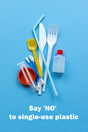 White single-use plastic and plastic drink straws on a blue background. Say no to single use plastic