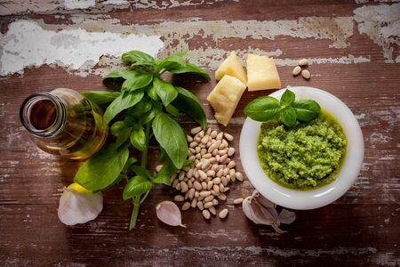 Green italian homemade sauce pesto made of ground basil, garlic, pine seeds, olives and pecorino sardo cheese. View on darken dooden background