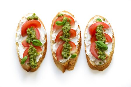 Toast with soft mascarpone cheese, tomatoes and fresh basil pesto. Top view, isolated on white background