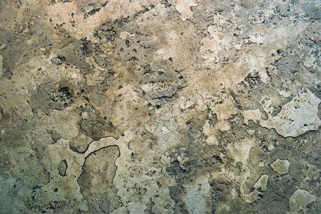 Textuur van de oude betonnen vloer in de onderdoorgang. Dit is een oude cementvloer op plekken en scheuren met kleine kiezels en puin. Stockfoto