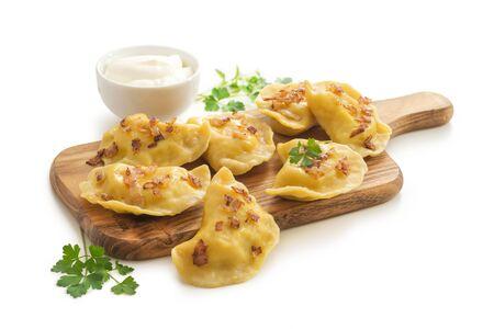Gelbe Teigtaschen mit Kurkuma, Röstzwiebeln und Petersilie, gefüllt mit Kartoffeln und weichem Fetakäse. Isoliert auf weißem Hintergrund