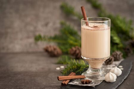 Christmas drink Eggnog in glass cups with a delicate foam, spices, cinnamon stick and candy on a dark moody background