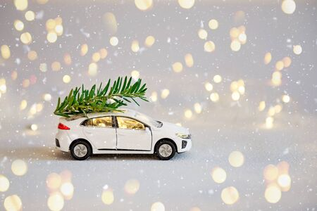 White toy car with a Christmas tree on the roof surrounded by a New Year's garland. Minimalism concept. Happy holidays greeting card