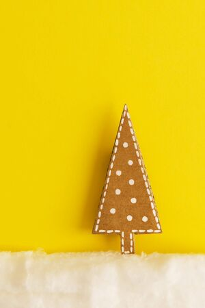 Christmas card with a picture of a Christmas tree made of cardboard in the snow of wool on a yellow background. Minimalism concept