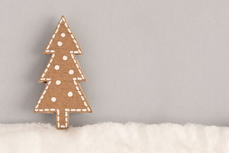 Christmas card with a picture of a Christmas tree made of cardboard in the snow of wool on a gray background. Minimalism concept