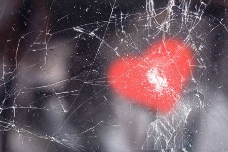 Mobile phone with cracks in the glass and a pattern in the shape of a heart on top