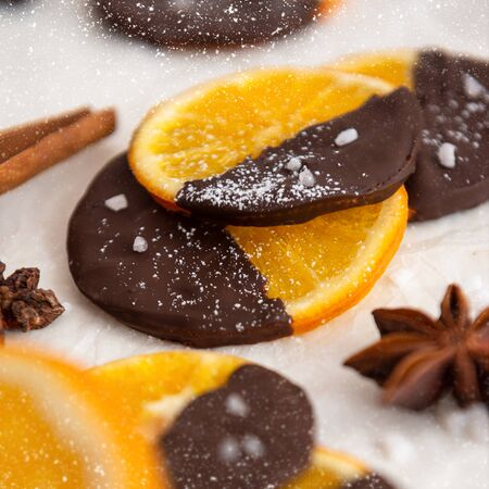 Candied orange in chocolate is a favorite Christmas treat for children and adults. Image of homemade candied orange dipped in chocolate. Top view