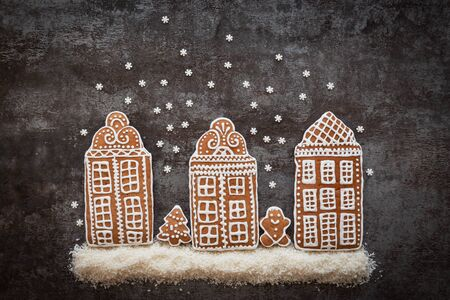 Gingerbread cookies in the shape of houses as a concept of a fabulous Christmas decoration. Top view.