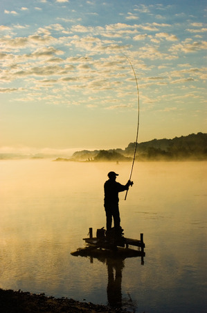 The fisherman fishes around in the morning at sunrise photo