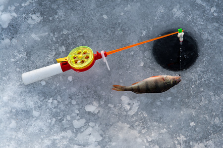 the rod for winter fishing lies near a hole photo