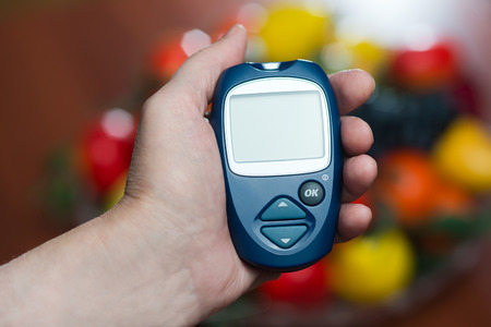 the hand of the elderly woman keeps the device for measurement of level of sugar in blood photo