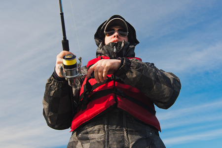 Fishing pole: fisherman in glasses with a fishing pole in the sky Stock Photo