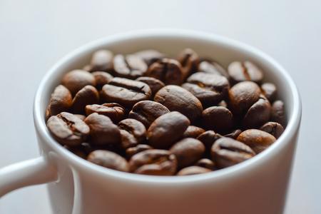 invigorate: coffee grains in a white mug on a table