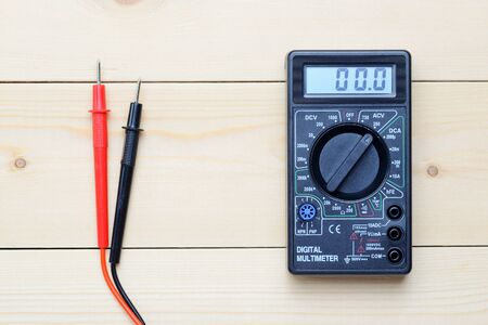 isolator switch: multimeter lies on a wooden board