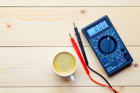 isolator switch: multimeter and cup of coffee Stock Photo