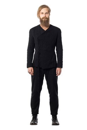 the young brutal man with a beard the attractive blonde with long hair in a black jacket and trousers, boots, on a white background to the utmost looks directly