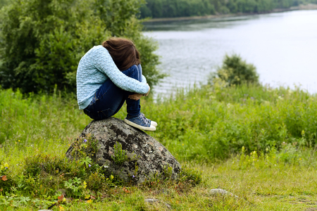 long depression: the sad girl in a blue jacket, jeans, gym shoes, with long hair sits on a stone against a grass, trees, water. Concept grief, despair, depression.