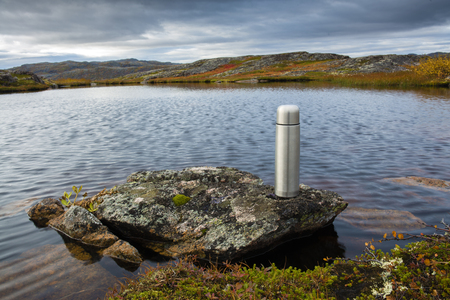The thermos stands on a rock by the lake in the north Stock Photo