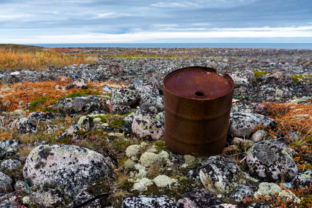 Rusty barrel on the shore of the Barents Sea