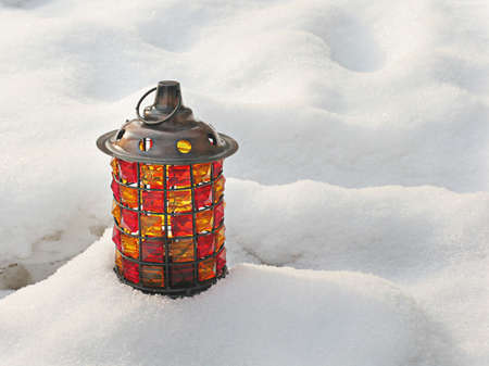 snowdrift: a lantern with a conflagrant candle stands in a snowdrift