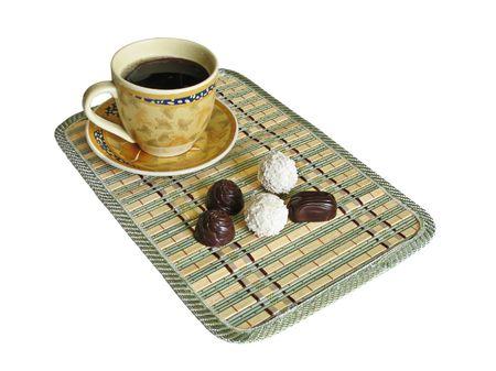 serviette: Kopje koffie met vijf chocolade snoepjes op een servetring Stockfoto