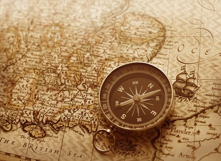 A compass lies on an age-old map Imagens