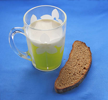 Cup of milk with the slice of rye bread on dark blue a table-cloth photo