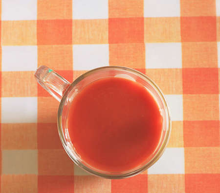 serviette: cup with tomato juice on the checked serviette Stock Photo