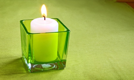 Conflagrant candle in green candlestick-glass with a mestome under text photo