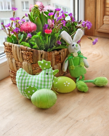 easter decorating of window by a rabbit and spring flowers Stock Photo