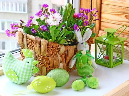 easter decorating of window by a rabbit and spring flowers Imagens
