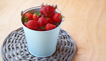 Strawberries in a grey bucket on the wooden table Stock Photo - 14554325