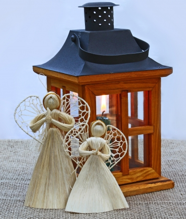 Handmade christmas decoration angels  from straw and lantern with a conflagrant candle. Products of mass production. photo