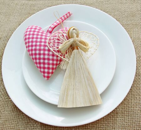 Romantic serving of festive table with a handmade decoration straw angel and heart photo