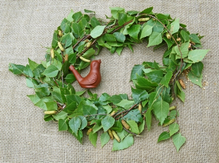 consuetude: A wreath from birch and cuckoo whistle on canvas background