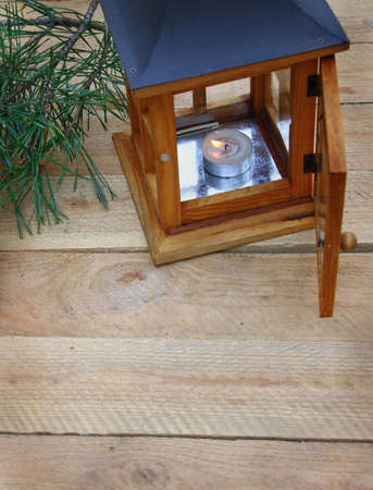 conflagrant: Wooden lantern with a conflagrant candle on wooden background